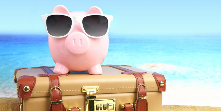 This is an image of a pig wearing sunglasses sitting on a suit case for last minute travel